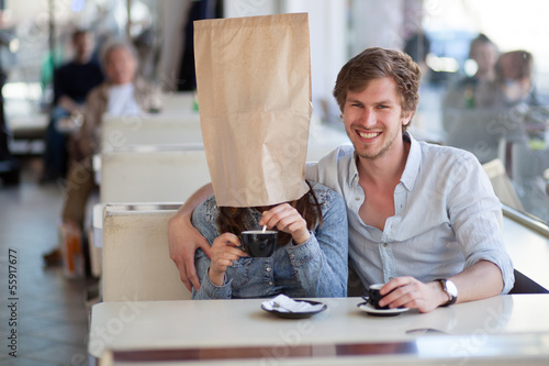 Young couple having coffee in a cafe. Young woman, wearing a pap