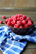 fresh and ripe raspberries in a bowl on a wooden table