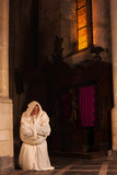 Kneeling monk in dark church