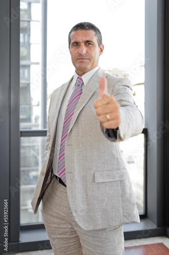 Uomo d'affari con pollice alzato in esterno
