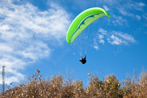 Green parglider flying in blue sky.