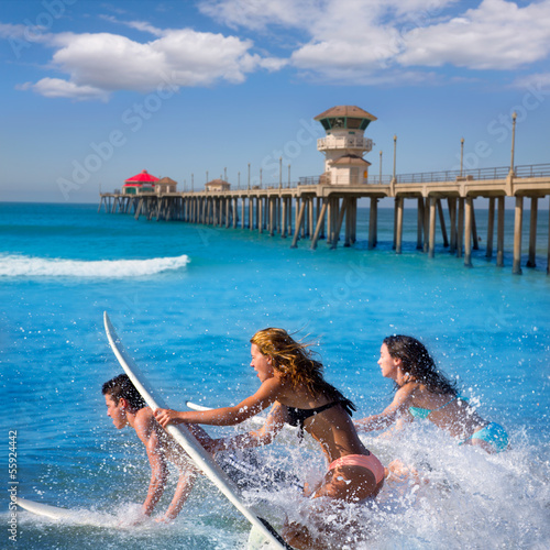 Teenager surfers running jumping on surfboards