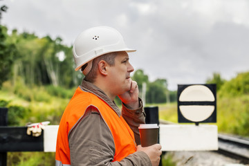 Worker with a coffee and cell phone on the railway in summer