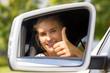 Junge Autofahrerin mit Daumen nach oben im Seitenspiegel
