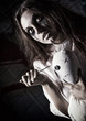 Horror shot: scary mad girl with moppet doll and needle in hands