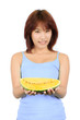 Isolated young asian woman with a piece of yellow watermelon
