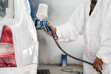 automobile engineer spraying paint on a white car
