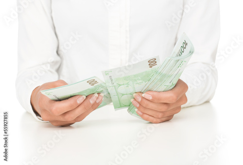 Close up of female hands counting money isolated on white