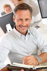 Portrait of smiling businessman writing on agenda