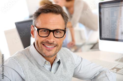 Leinwanddruck Bild Portrait of smiling businessman with eyeglasses