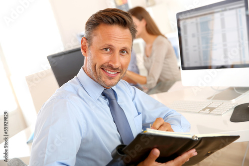 Portrait of handsome businessman holding agenda