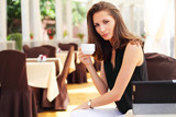 Image of young beautiful woman drinks coffee in cafe