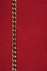 Gold chain lying on red fabric