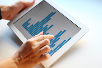 Image of human hand pointing at touchscreen with business graph