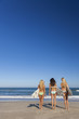 Three Beautiful Women Surfers In Bikinis With Surfboards At Beac