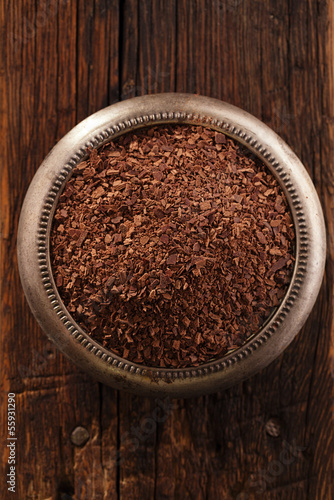fine grated chocolate in bowl on wood , shallow dof
