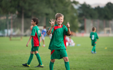 little boy showing result on football match
