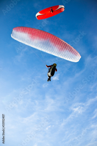 Two paragliders flying in blue sky.
