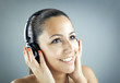 Portrait of a young woman with headphones listening music over g