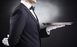 Fototapety Waiter holding empty silver tray over black background