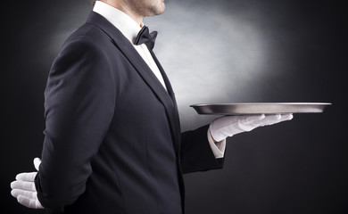 Waiter holding empty silver tray over black background