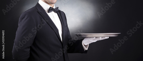Waiter holding empty silver tray over black background - 55934692