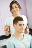Cheerful hairdresser in beauty salon