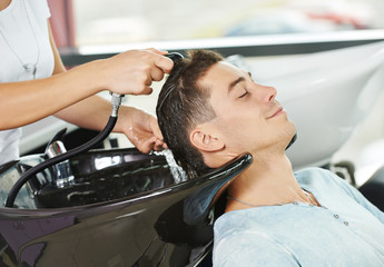 Man hair washing in hairdressing salon