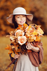 Young fashion woman  walking in autumn park with a bouquet of fa
