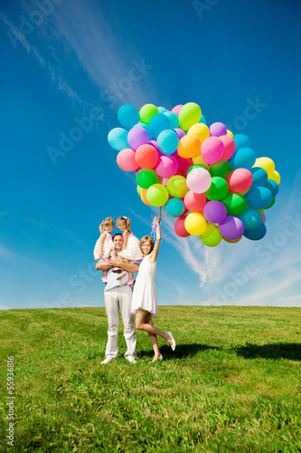 Happy family holding colorful balloons. Mom, dad and two daughte
