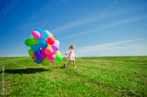 Little girl holding colorful balloons. Child playing on a green - 55936862