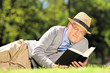 Senior man lying on a grass and reading a book in a park