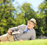 Senior gentleman with hat lying on a grass with a book in park
