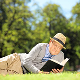Senior man with hat lying on a grass reading a book in a park