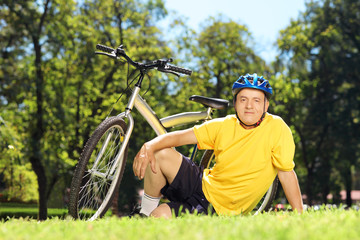 Mature man in sportswear sitting on a grass with his bike
