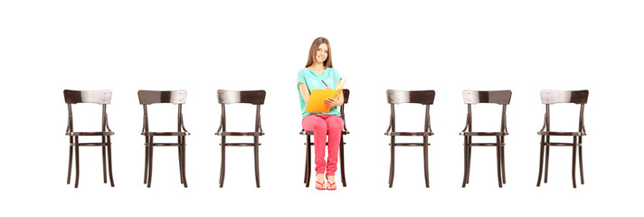 Smiling female student sitting on a wooden chair writing notes