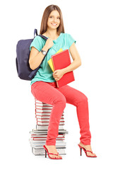Smiling student with bag holding notebooks and sitting on books