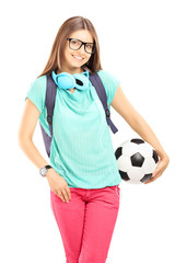 Young female student with backpack holding a soccer ball