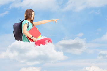 Female student with bag pointing with her finger on a cloud