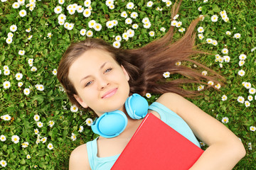 Young female with book and headphones lying on a grass