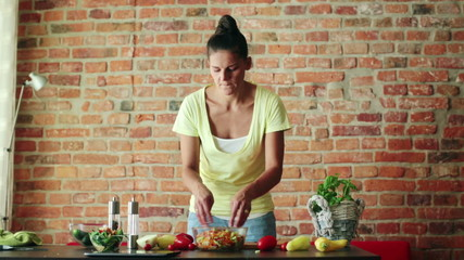 Woman mixing, preparing salad in kitchen