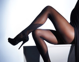 Sexy female legs in erotic stocking and high heels