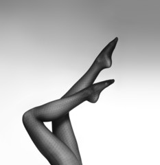 Black and white photo of beautiful female legs in stockings