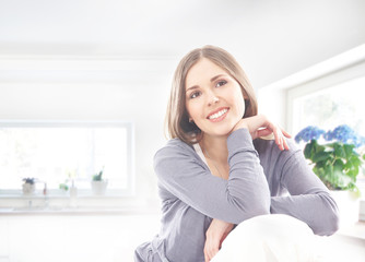 A young and happy brunette woman relaxing on a home interior