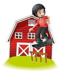A boy skating in front of the red barnhouse