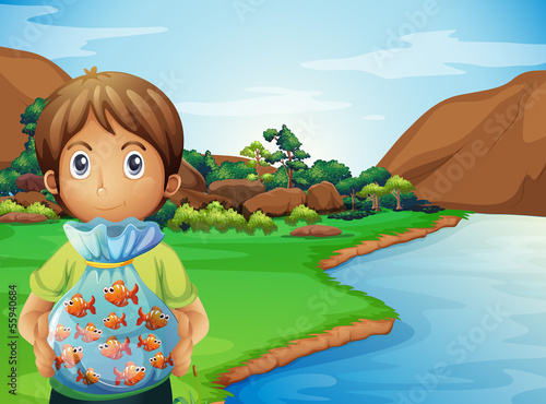 A young boy at the riverbank holding a plastic full of fishes