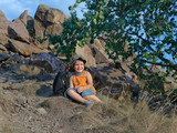 Little boy resting on the mountain in summer