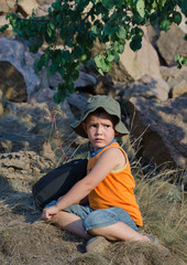 Young boy waiting alongside his rucksack