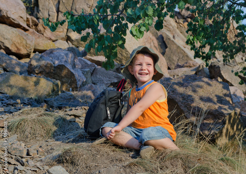 Happy little boy resting after hiking expedition