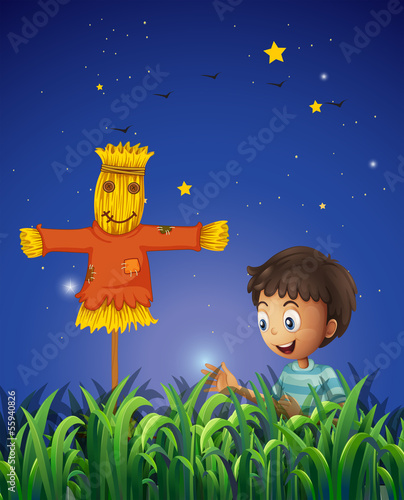 A boy at the farm with a scarecrow